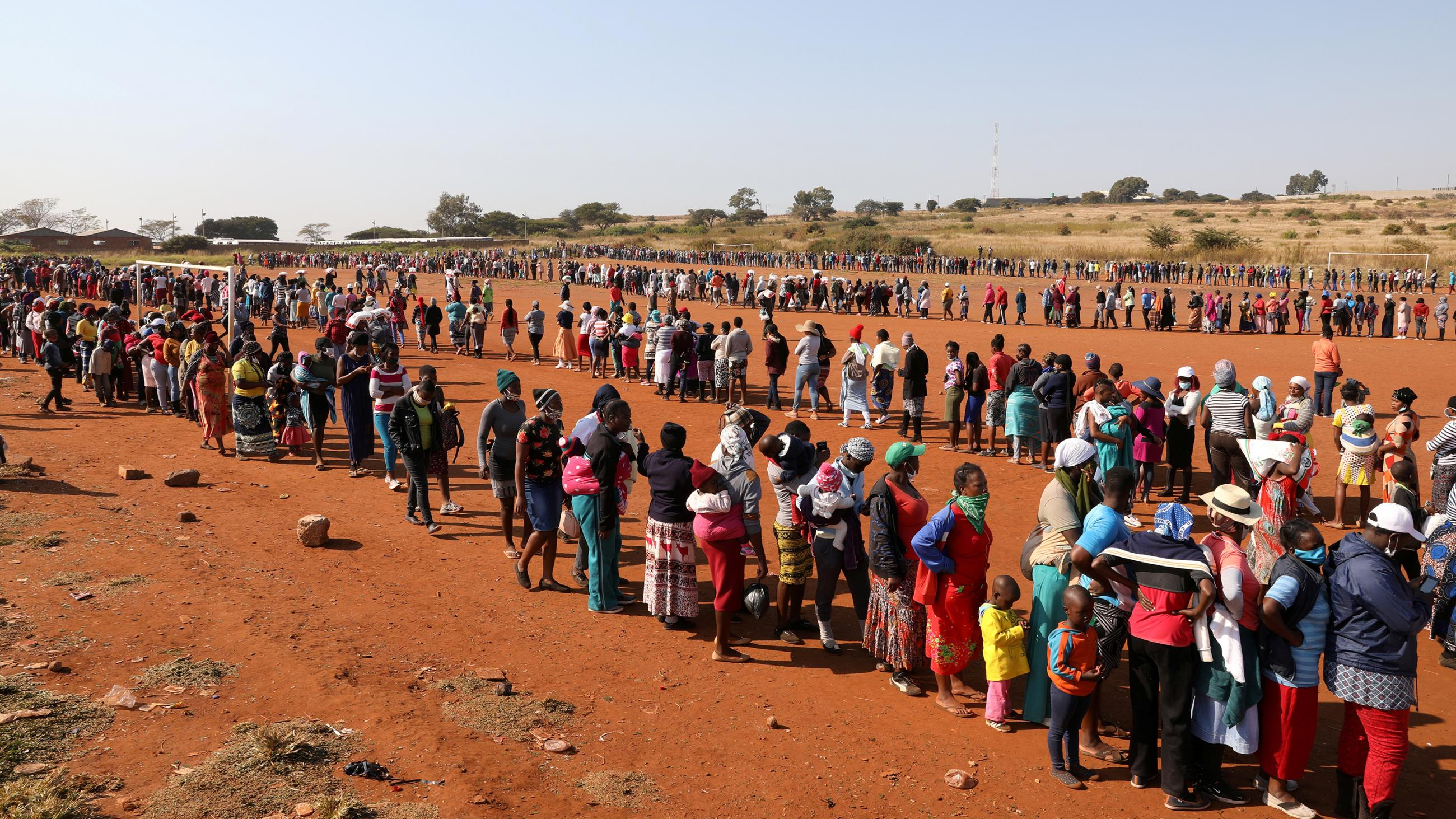The photo is taken from a high vantage overlooking a huge crowd of people standing on line in a red soil dry plain.