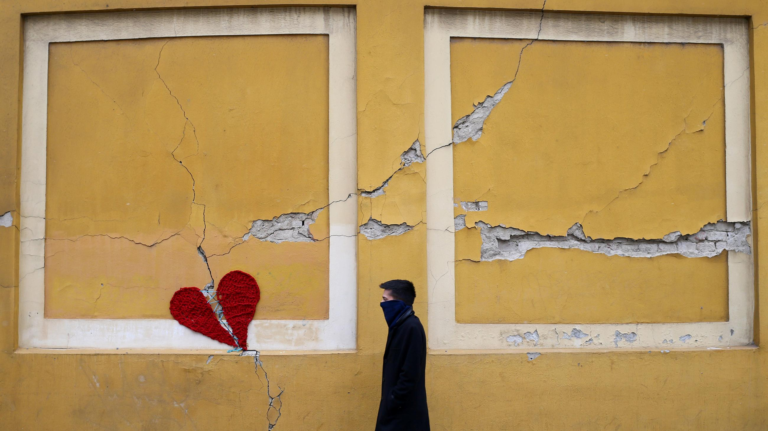 The photo shows a man walking past the heart on the side of a building that appears cracked.