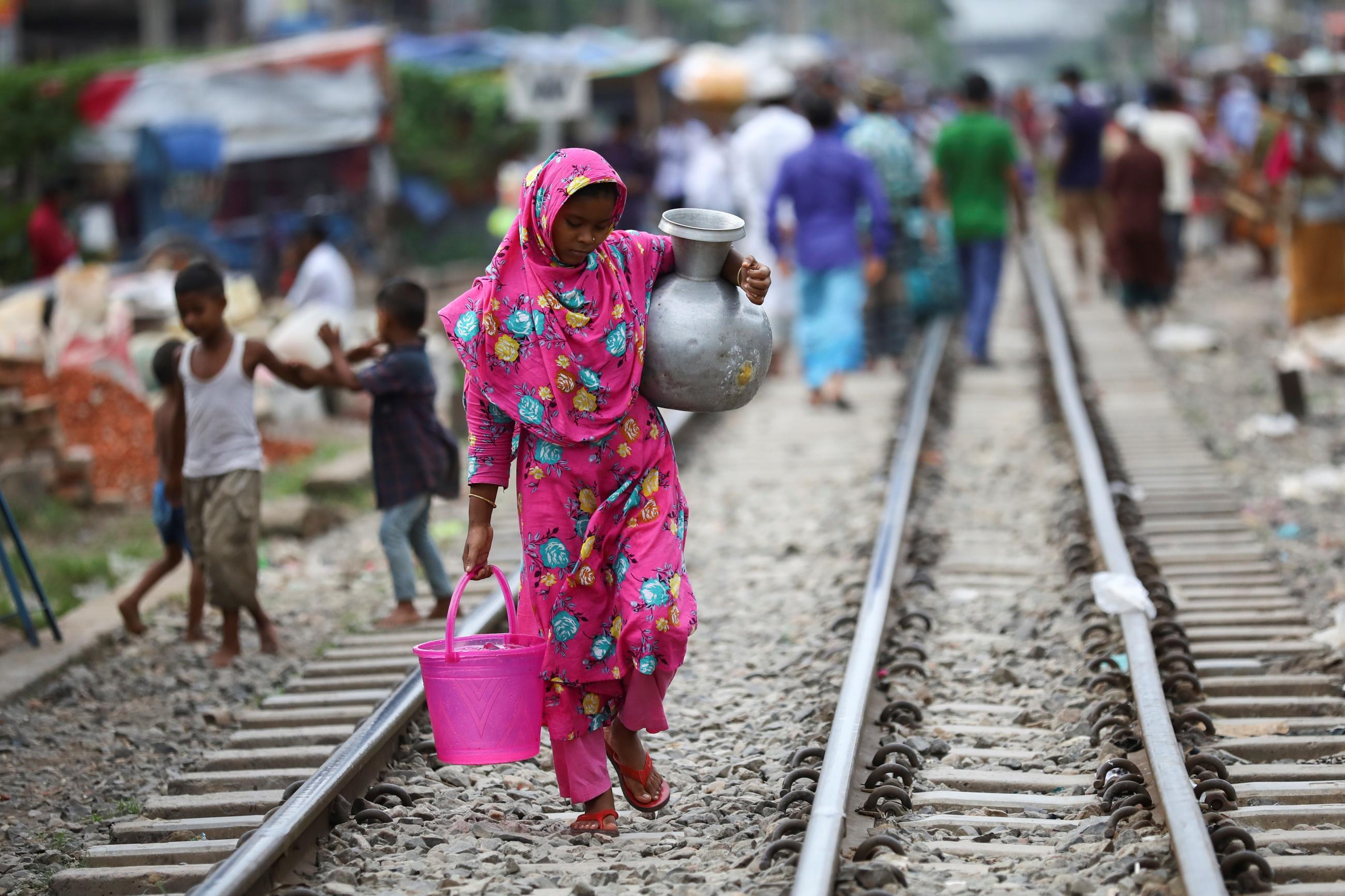 A slum dweller woman carries drinking water in Dhaka, Bangladesh, September 15, 2020. REUTERS/Mohammad Ponir Hossain