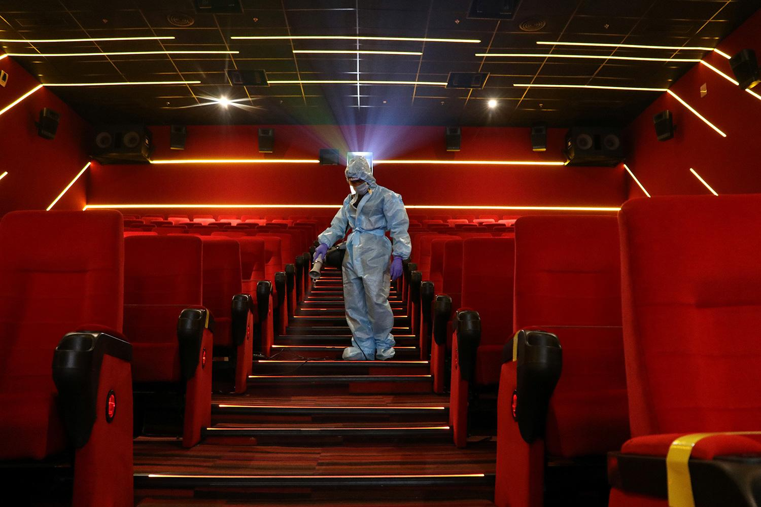 Addressing pandemic preparedness after COVID-19 will require going deeper than the surface. Here a worker sanitizes surfaces inside the Inox Leisure movie theatre in Mumbai, India, October 13, 2020. The photo is striking, showing a worker spraying disinfectant wearing a blue suit descending down a theater staircase where all the seats and carpet are bright red. REUTERS/Niharika Kulkarni