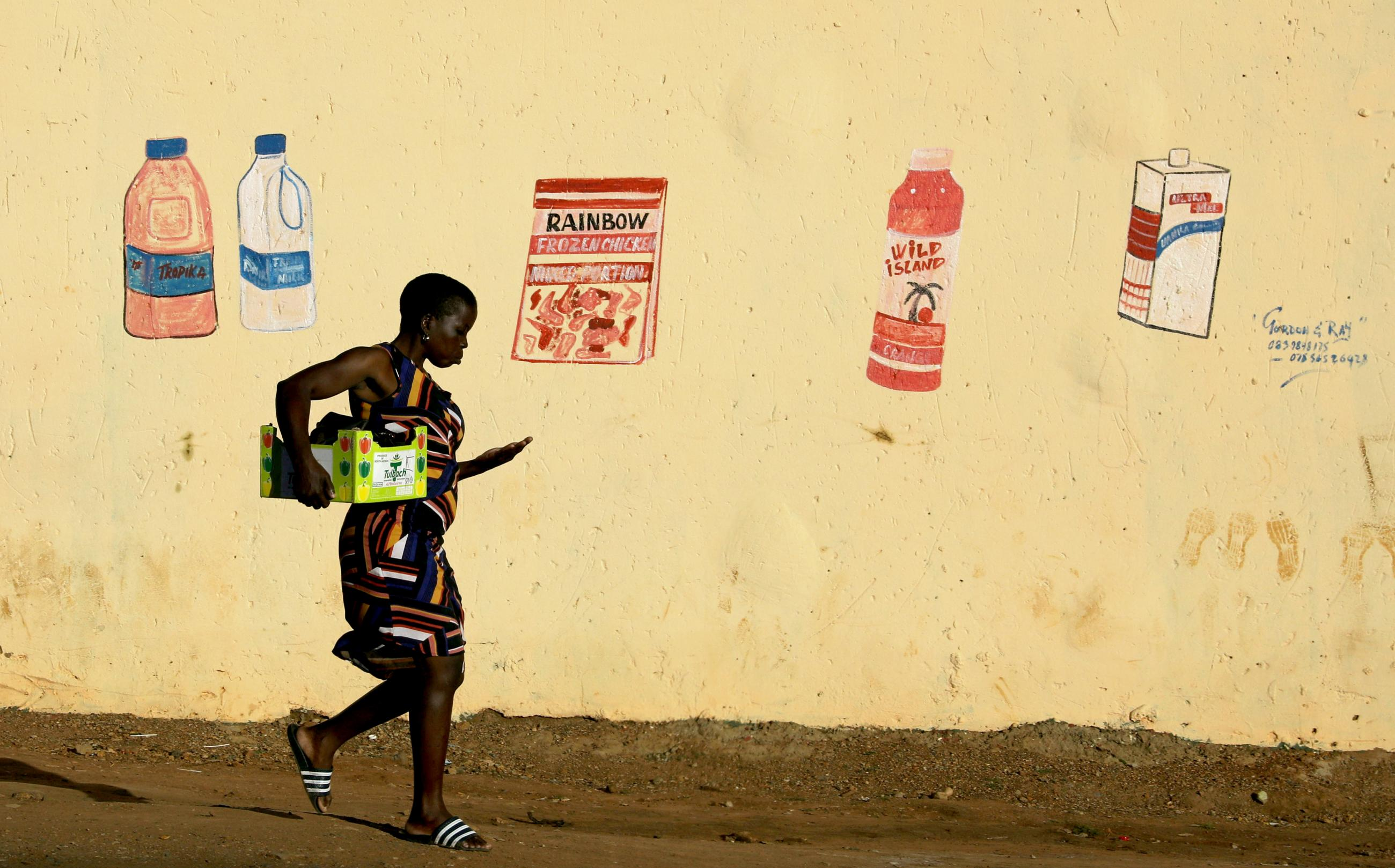 "A woman counts her change as she leaves a convenience store, or ""spaza shop"", with a mural depicting grocery items, during a nationwide lockdown for 21 days to try to contain the coronavirus disease (COVID-19) outbreak, at the Elias Motsoaledi informal settlement, South Africa, April 7, 2020."