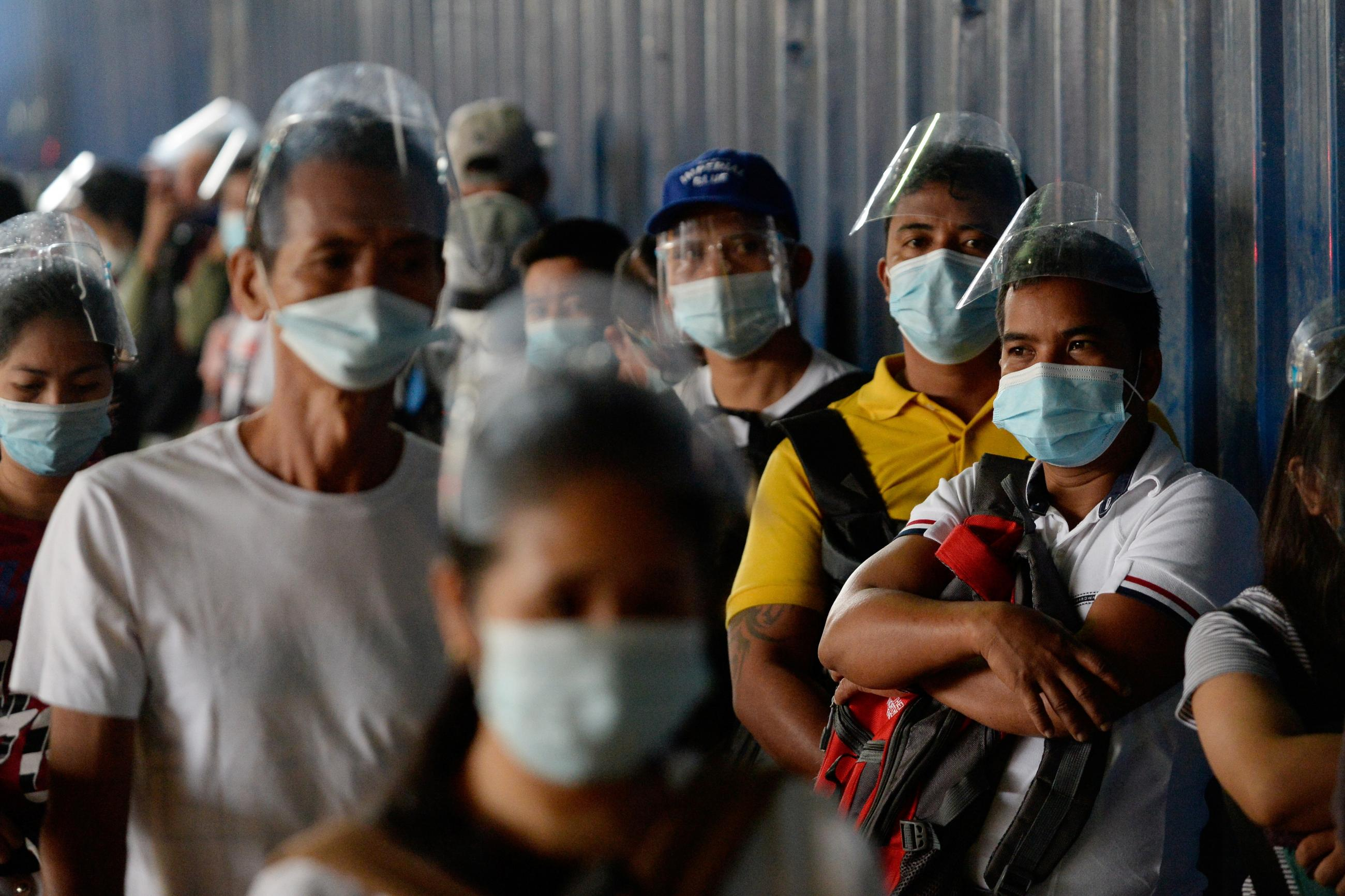 People wearing face masks as protection against the coronavirus disease (COVID-19) queue outside a government office, in Caloocan City, Metro Manila, Philippines, February 1, 2021.