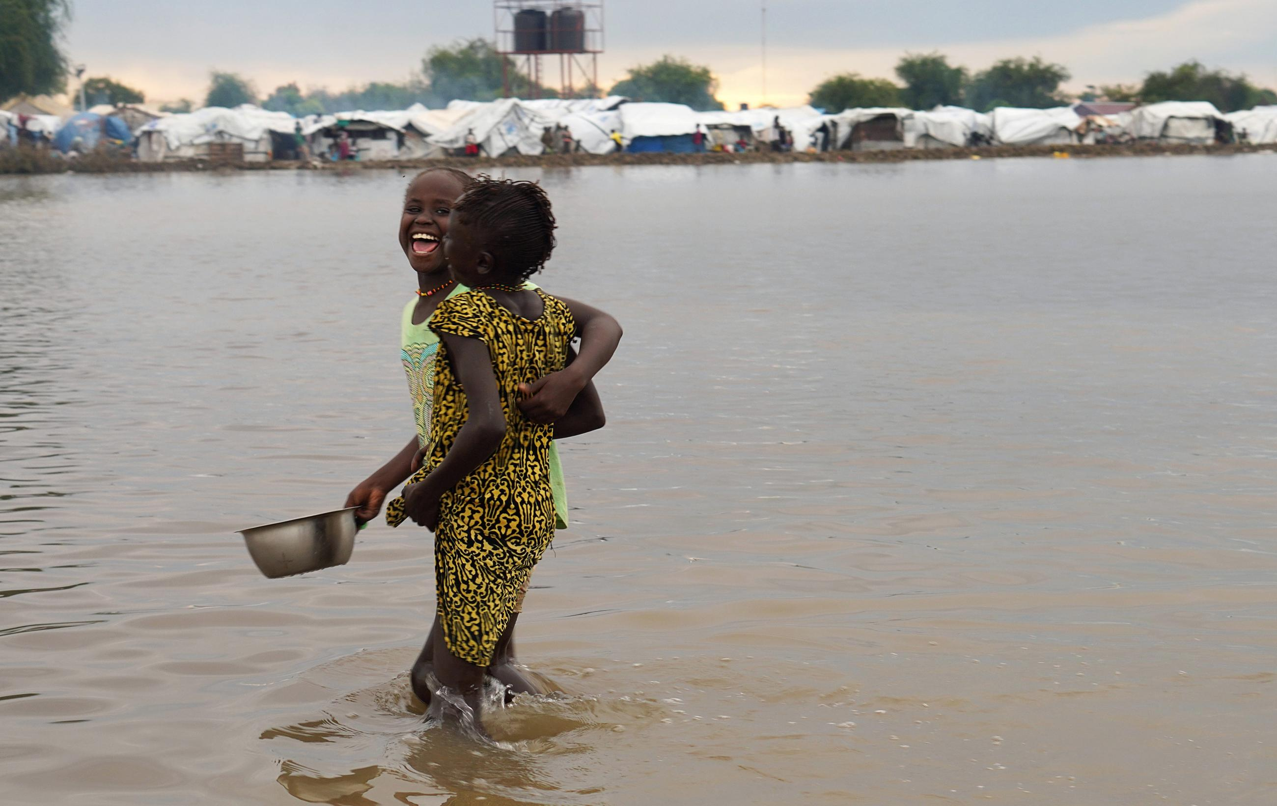 Displaced children laugh as they wade through floodwaters after the River Nile broke the dykes in Pibor, Greater Pibor Administrative Area, South Sudan October 6, 2020.