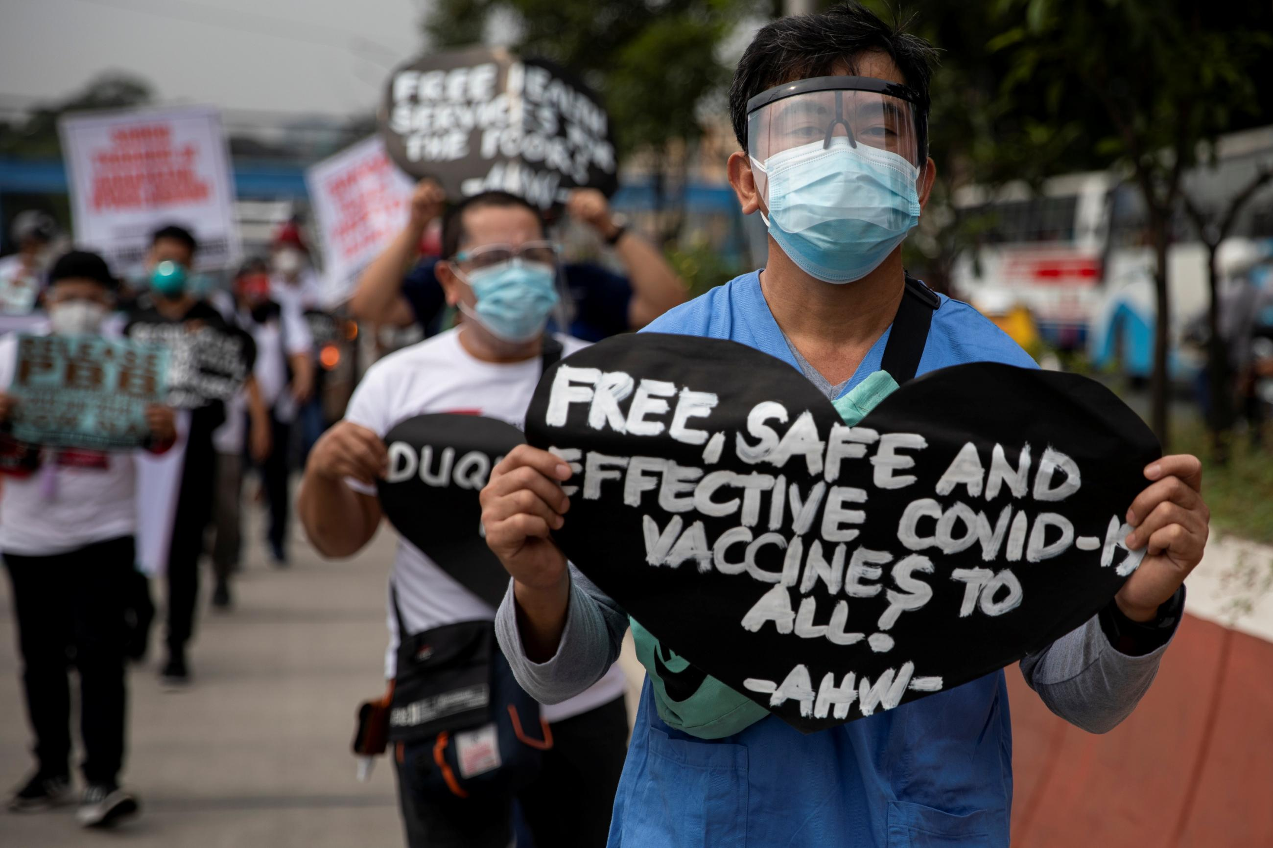 A health worker holds a placard calling for free, safe, and effective COVID-19 vaccines during a protest amid the coronavirus outbreak in Quezon City, Metro Manila, Philippines, February 15, 2021