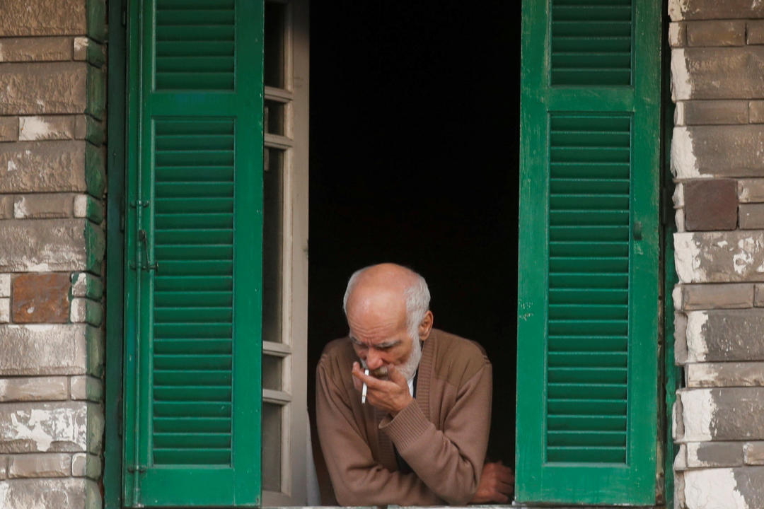 A man looks from the window of his home as he smokes a cigarette amid the coronavirus pandemic in Alexandria, Egypt on December 3, 2020.