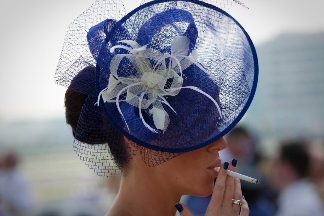 A spectator smokes a cigarette as she waits for the start of the Dubai World Cup racehorse at Meydan Racecourse in Dubai, United Arab Emirates on March 29, 2014. REUTERS/Caren Firouz