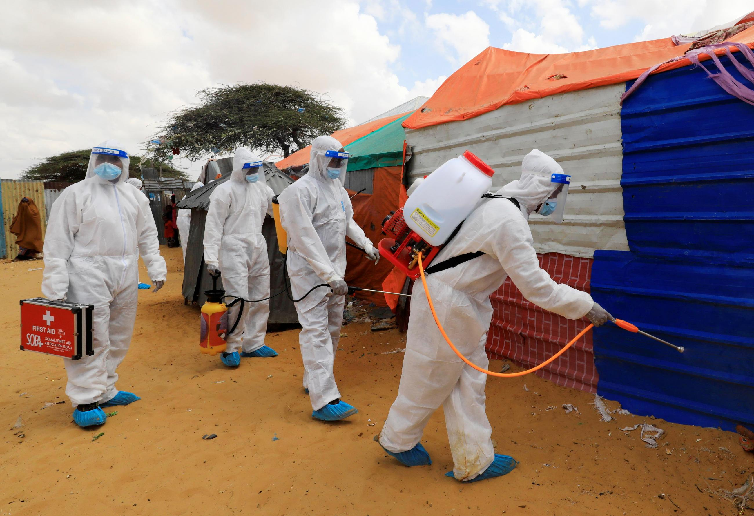 Men wearing body-covering white suits and are members of Somali First Aid Association spray disinfectants in an effort to stop the spread of COVID-19 at a camp for internally displaced people in Mogadishu, Somalia on April 18, 2021