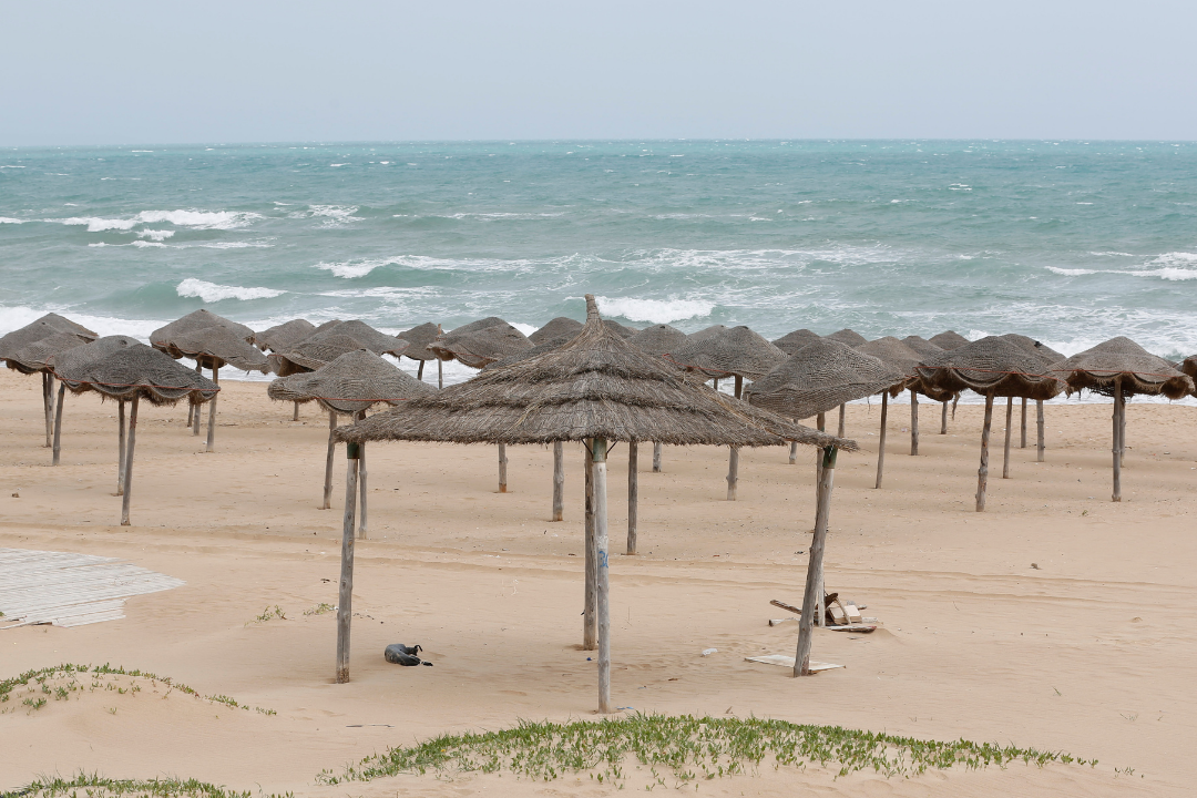 A deserted beach with umbrellas made of natural materials is pictured during an extended lockdown aimed at stemming the spread of COVID-19 in April 2020 in Tunis, Tunisia.