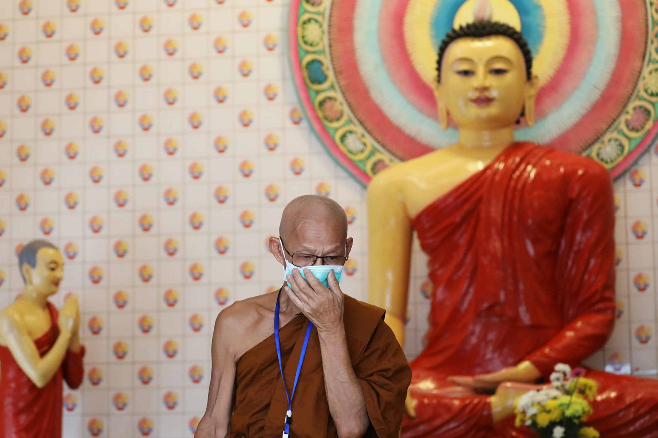 A Buddhist monk adjusts his protective face mask before a blessing ceremony for the people affected by the COVID-19 coronavirus outbreak, at a temple in Kuala Lumpur, Malaysia on February 22, 2020. This is a striking image with the monk in the foreground and some very colourful Buddhist temple features in the background. REUTERS/Lim Huey Teng