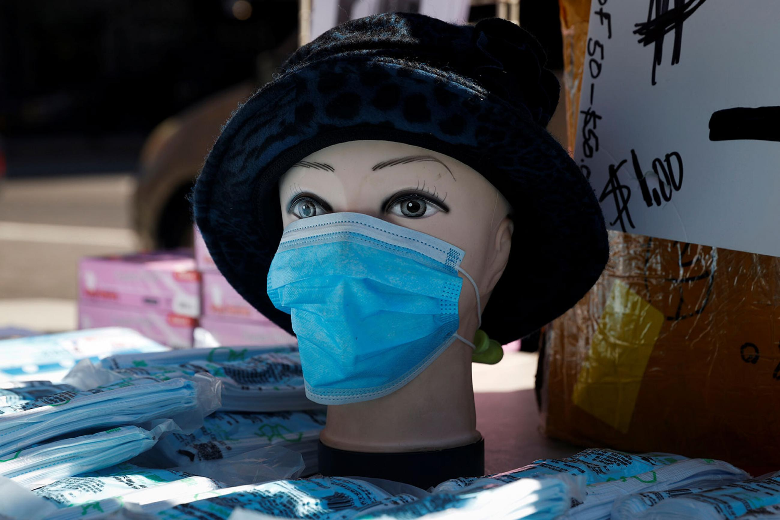 A mannequin with a surgical mask on display where a vendor sells packages of masks on a corner in the Chelsea neighborhood during the outbreak of the coronavirus in New York City on March 27, 2020. The photo shows a mannequin wearing a blue mask. REUTERS/Mike Segar