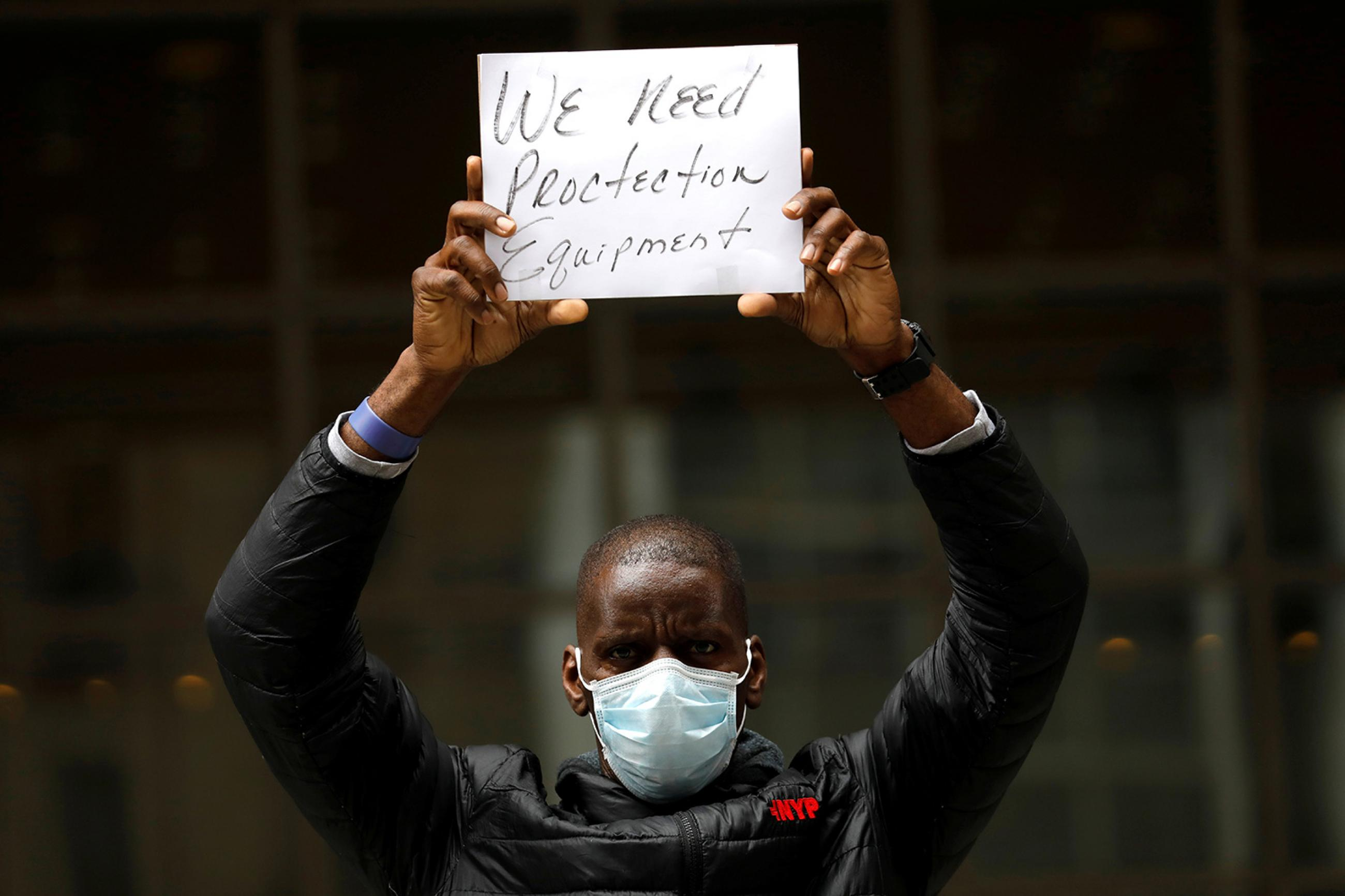 """A health worker in a demonstration calling on federal and local authorities to provide more Personal Protective Equipment outside New York-Presbyterian Medical Center in Manhattan on April 9, 2020. The image shows a man wearing a mask and holding a small sign above his head that says, """"We need protection equipment."""" REUTERS/Mike Segar"""