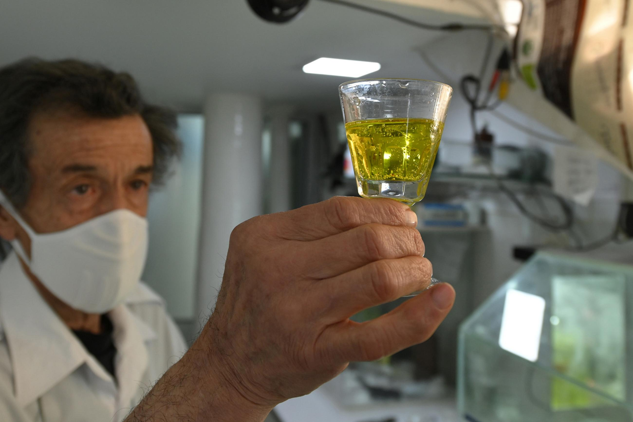 A pharmacist holds a medicine containing chlorine dioxide at the Farmacia Boliviana, amid the outbreak of the coronavirus disease (COVID-19), in Cochabamba, Bolivia, on July 21, 2020. The photo shows a man wearing a mask holding up a wine glass filled with a bright yellow liquid. REUTERS/Danilo Balderrama