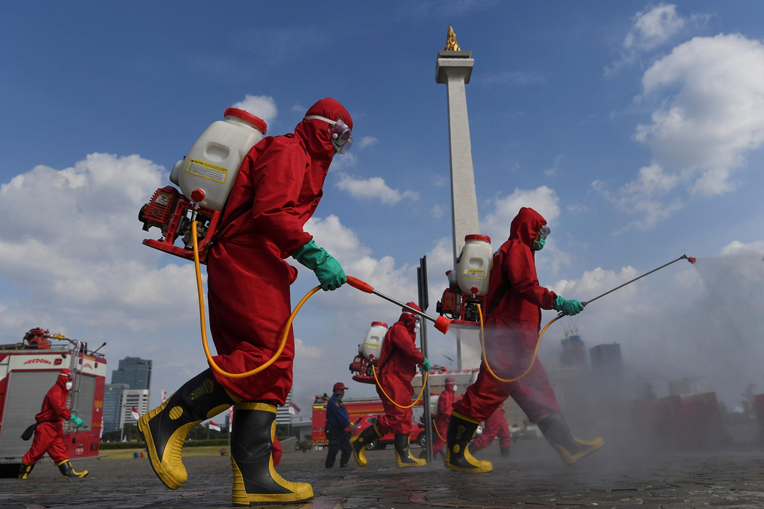 Firefighters wearing protective suits spray disinfectant at the National Monument area to prevent the spread of the coronavirus disease (COVID-19) in Jakarta, Indonesia, on June 17, 2020. Photo shows several workers in bright red protective suits walking though an open area spraying from tanks they carry on their backs. A monument can be seen in the background. REUTERS/Antara Foto/Wahyu Putro
