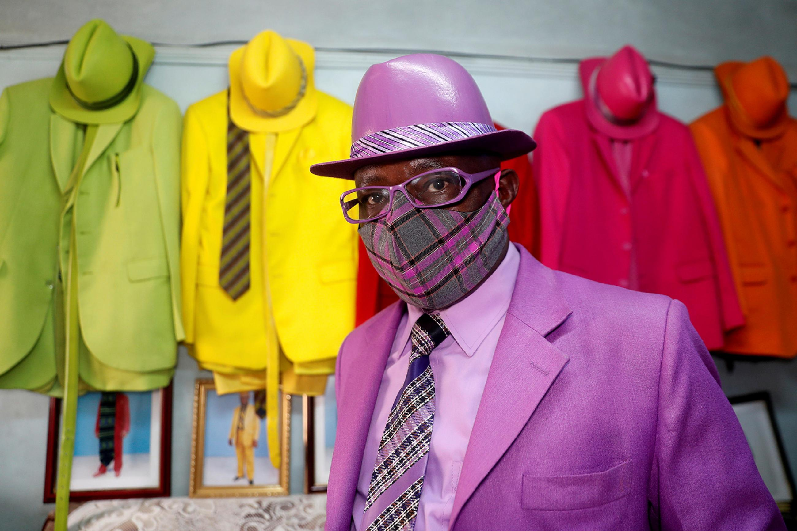 The author argues for pandemic responses that do not sacrifice long-term health projects—just as Kenyan fashionista James Maina Mwangi, on July 30, 2020, blends 160 stylish suits with sensible masks. Picture shows James smartly dressed in a well-appointed purple suit with a matching mask. In the background are striking blue and orange and green suits hanging on the wall. REUTERS/Thomas Mukoya