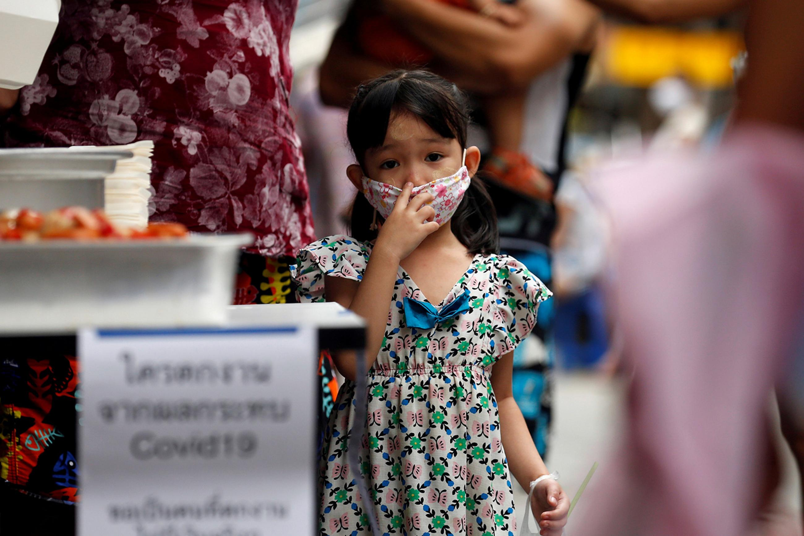 A girl from a migrant worker family that came to Thailand from Myanmar and lost their jobs due to COVID-19, lines up for free food in Bangkok, Thailand, on April 23, 2020. The photo shows a small girl wearing a facemask looking at the camera. REUTERS/Soe Zeya Tun