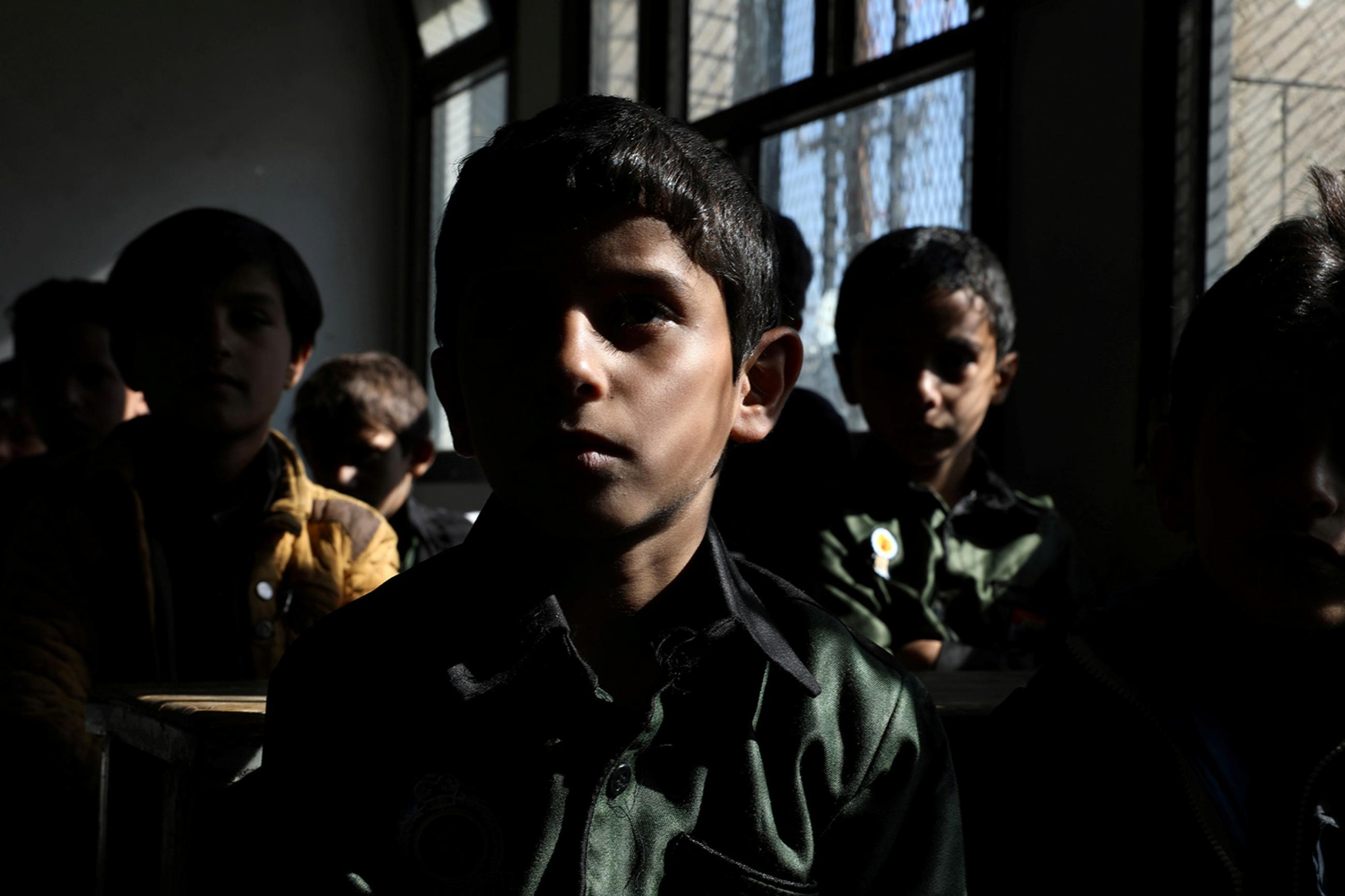 Students attend a class at the beginning of the school year amid fears of the spread of the coronavirus disease (Covid-19) in Sanaa, Yemen October 18, 2020. The photo shows a darkened classroom with several students facing the camera. REUTERS/Khaled Abdullah