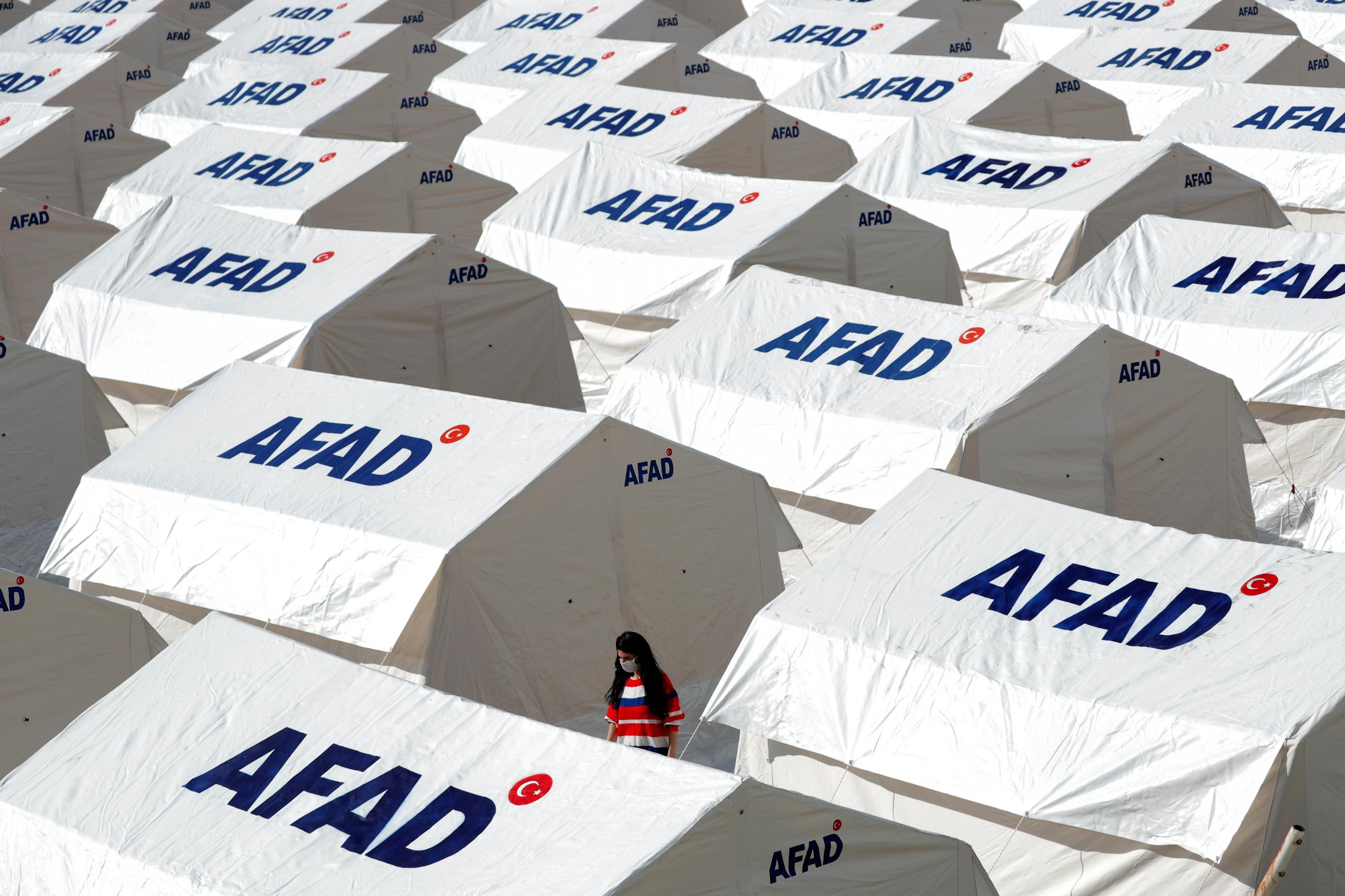 A woman walks amid a tent city set up by Turkey's Disaster and Emergency Management Presidency (AFAD) after an earthquake in the Aegean port city of Izmir, Turkey, November 1, 2020.