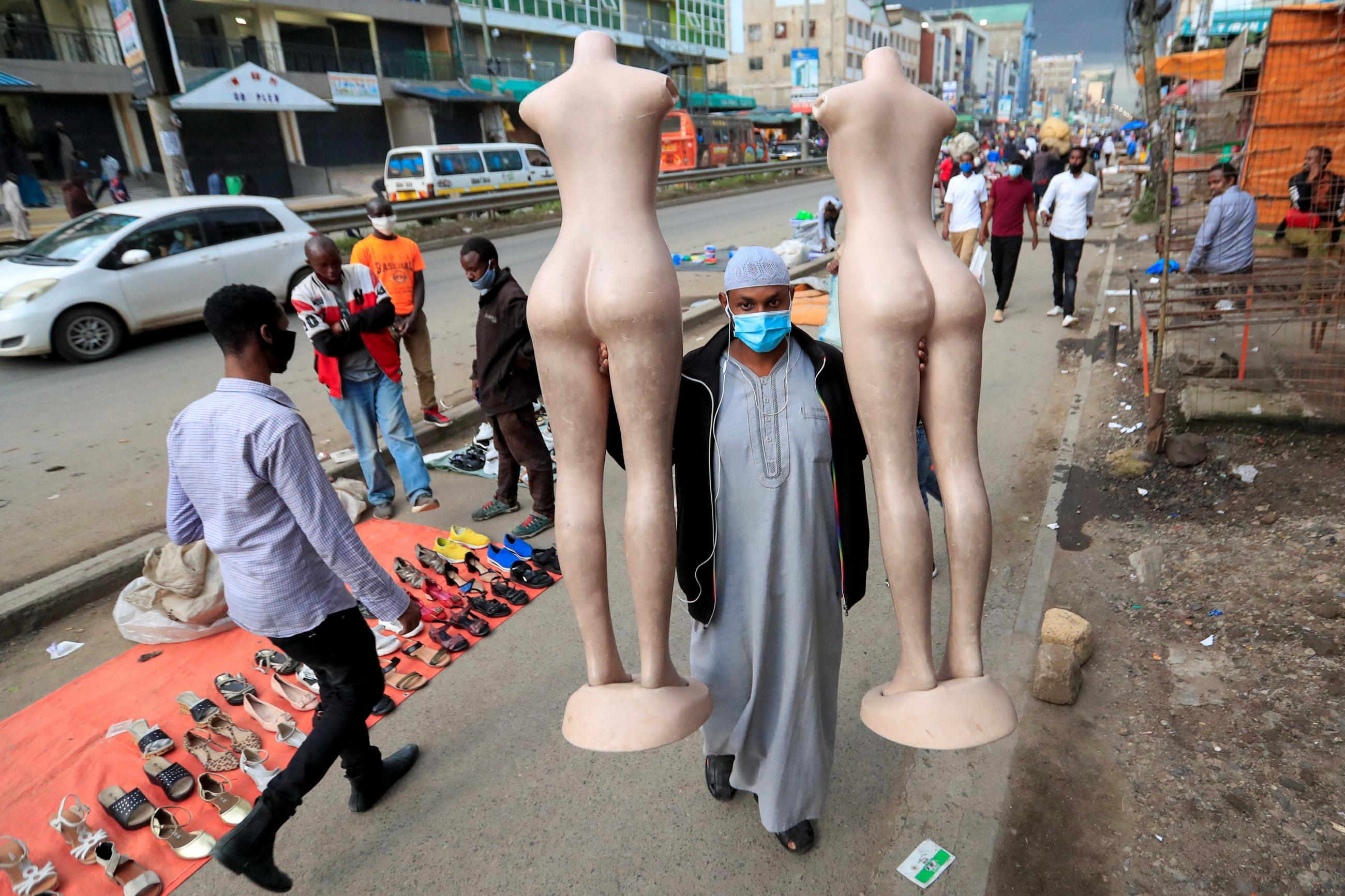 A masked-trader carriers two female-form mannequins as he closes his business ahead of the lockdown resulting from the COVID-19 pandemic in Nairobi, Kenya.