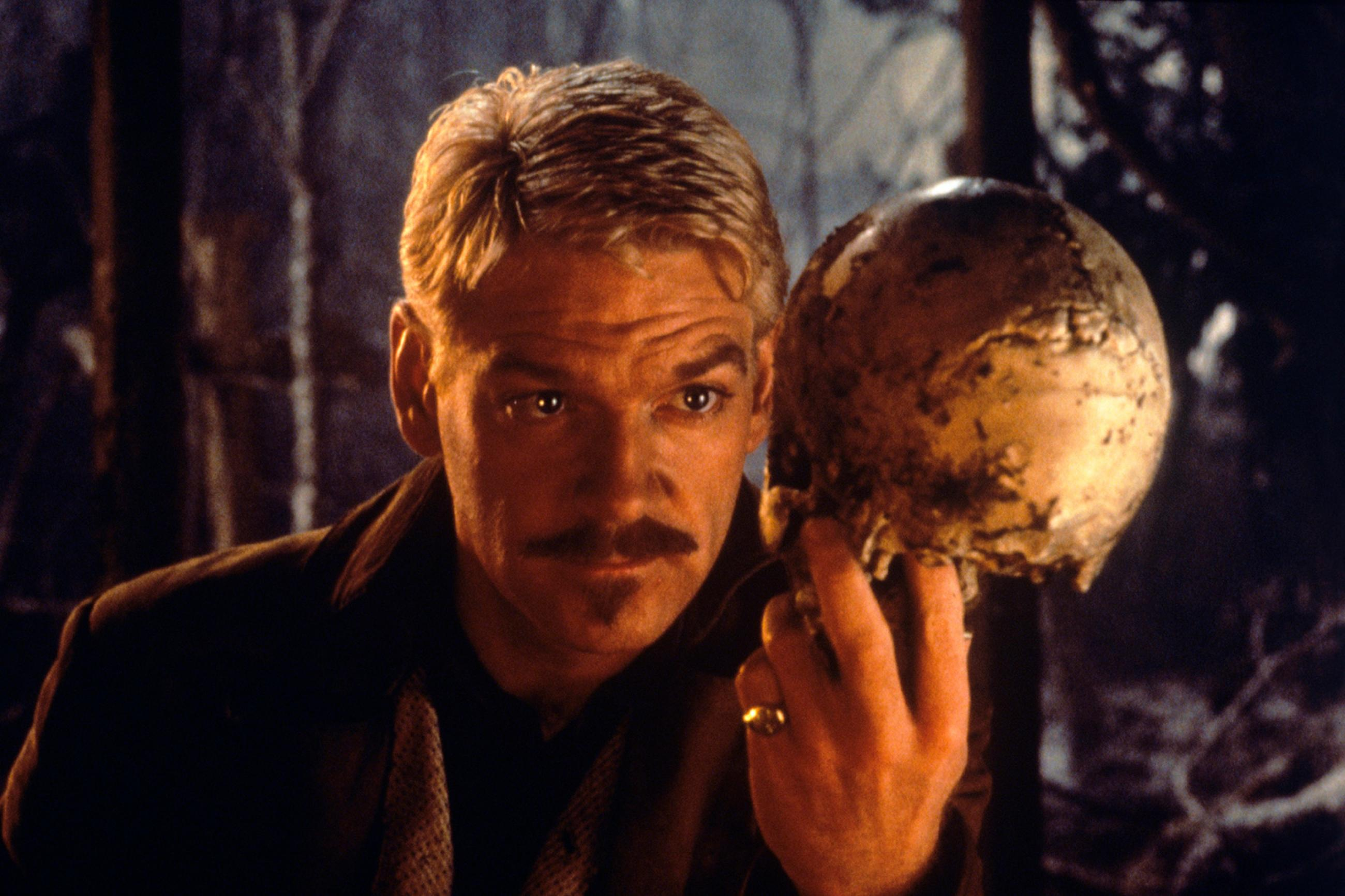 """The story title comes from Shakespeare: """" The heart-ache and the thousand natural shocks / That flesh is heir to""""—photo is of British actor Kenneth Branaugh holding a skull in the film Hamlet (1996). The photo shows the actor bathed in orange light and dressed in period garb holding a skull in a contemplative pose. GETTY IMAGES/Mondadori"""