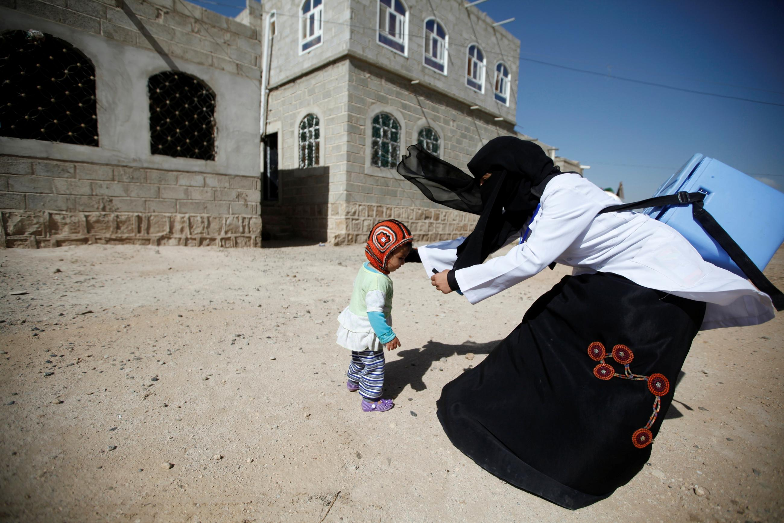 A health worker holds a girl to give her polio vaccination drops during a house-to-house anti-polio vaccination campaign in Yemen's capital Sanaa, April 12, 2016.