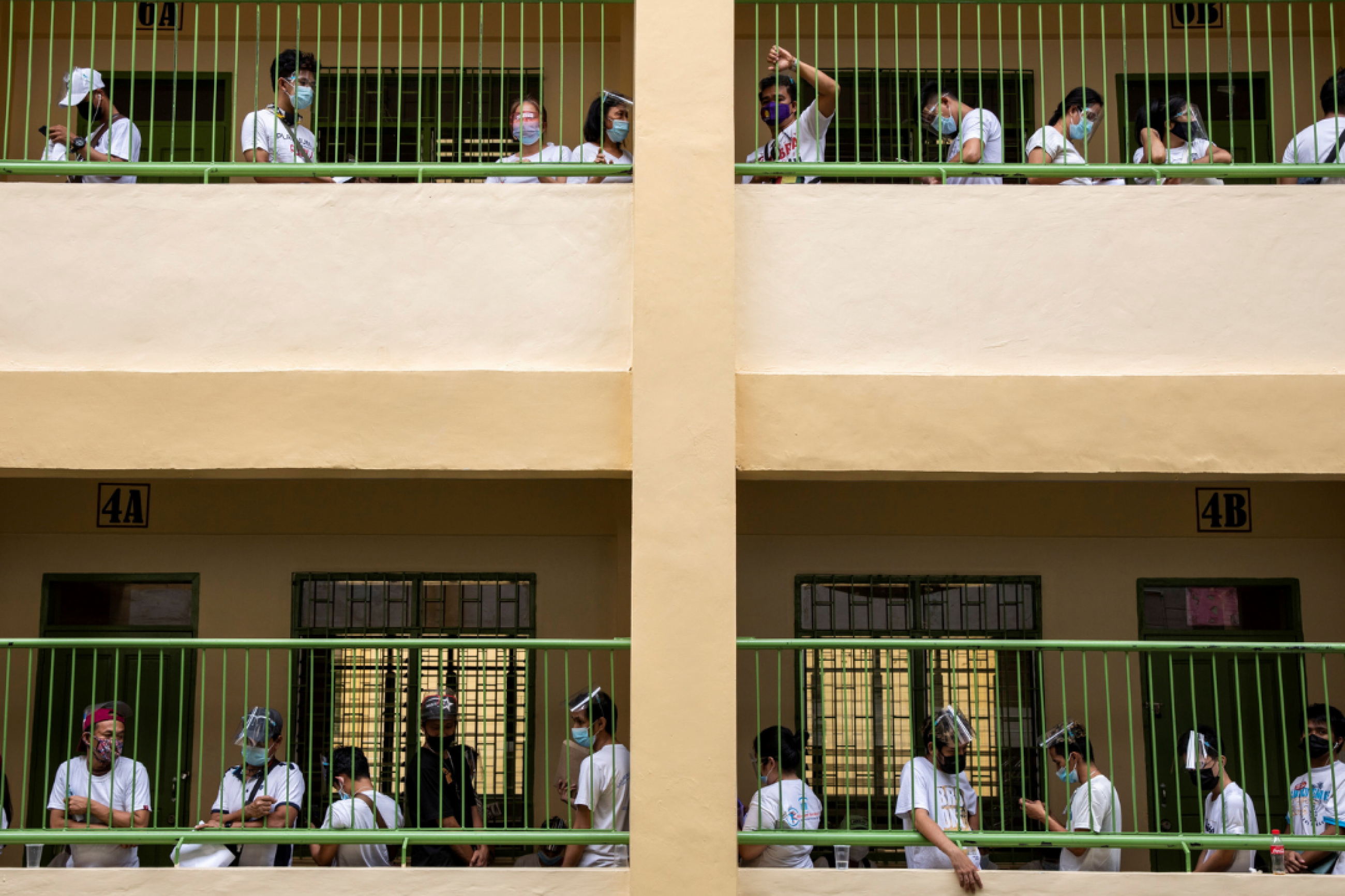 People whose jobs were affected by COVID-19 restrictions wait in lines to receive cash assistance from the government, at an elementary school in Quezon City, Metro Manila, Philippines, April 12, 2021.