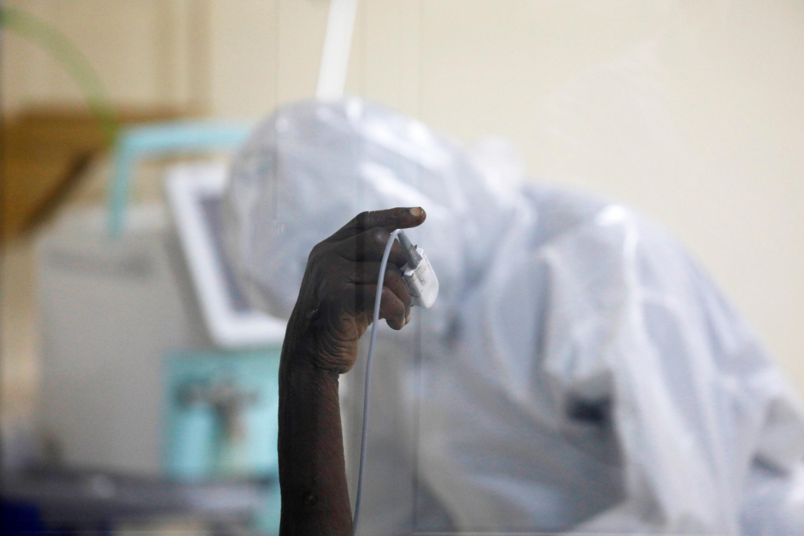 A coronavirus disease patient holds up his hand inside the COVID-19 ICU of Machakos Level 5 Hospital, in Machakos, Kenya October 28, 2020.