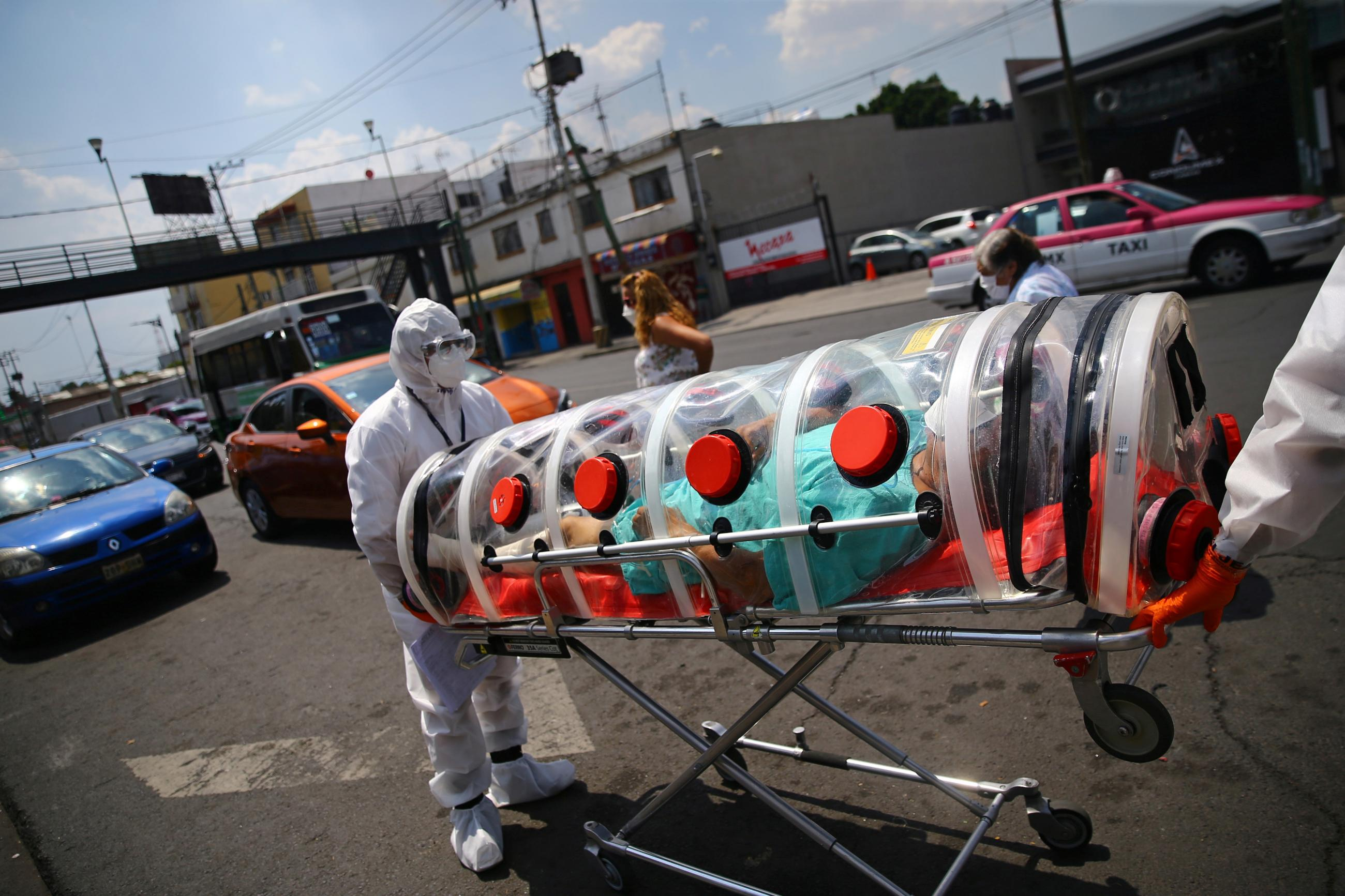 A patient suffering from COVID-19 and diabetes, is pictured inside a capsule as Red Cross paramedics transfer him from a hospital to another in Mexico City, Mexico, on June 8, 2020