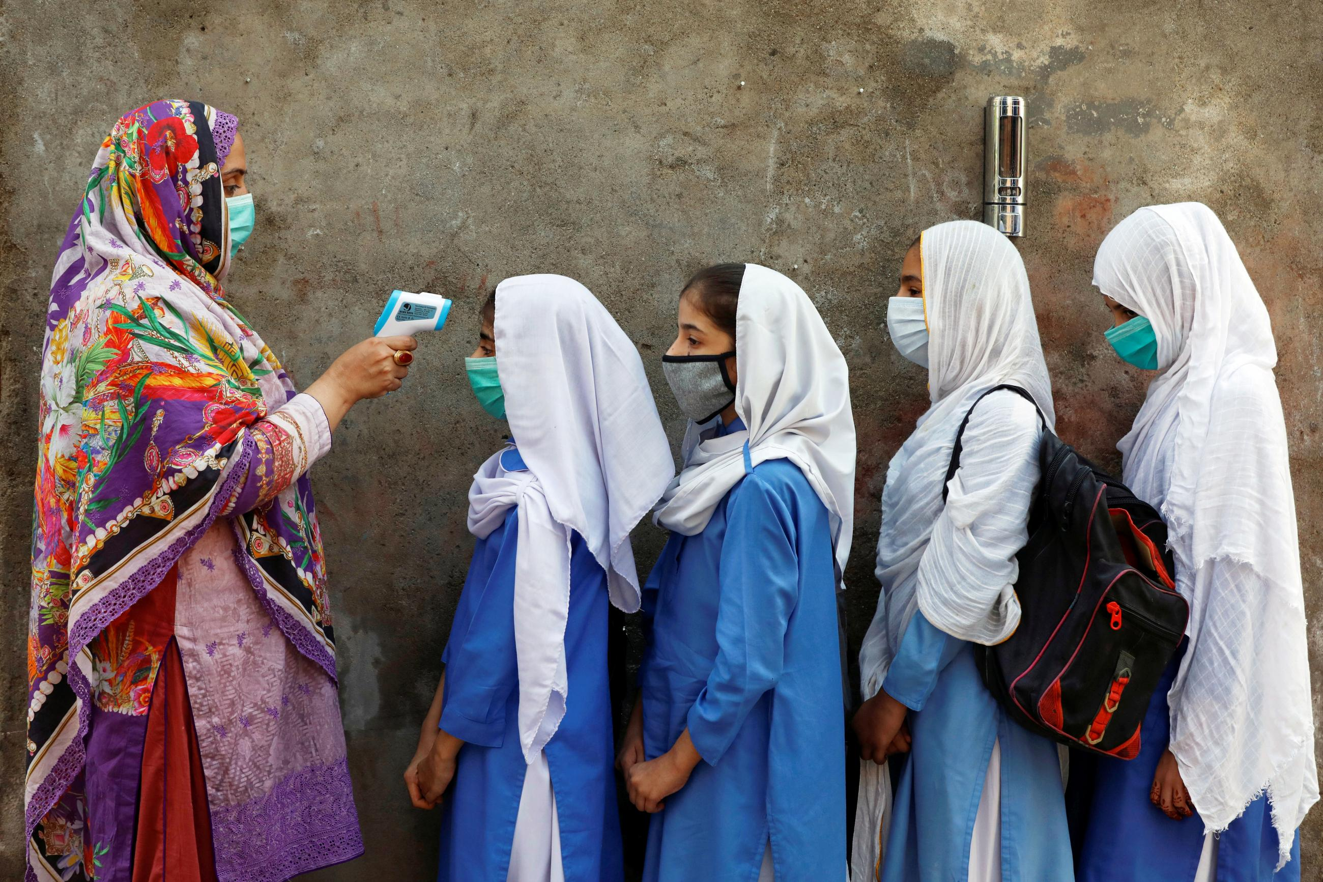 Students wear protective face masks as they have their temperature checked before entering a class, after the government allowed the reopening of schools from grade six to eight amid the coronavirus disease (COVID-19) pandemic, in Peshawar, Pakistan September 23, 2020.