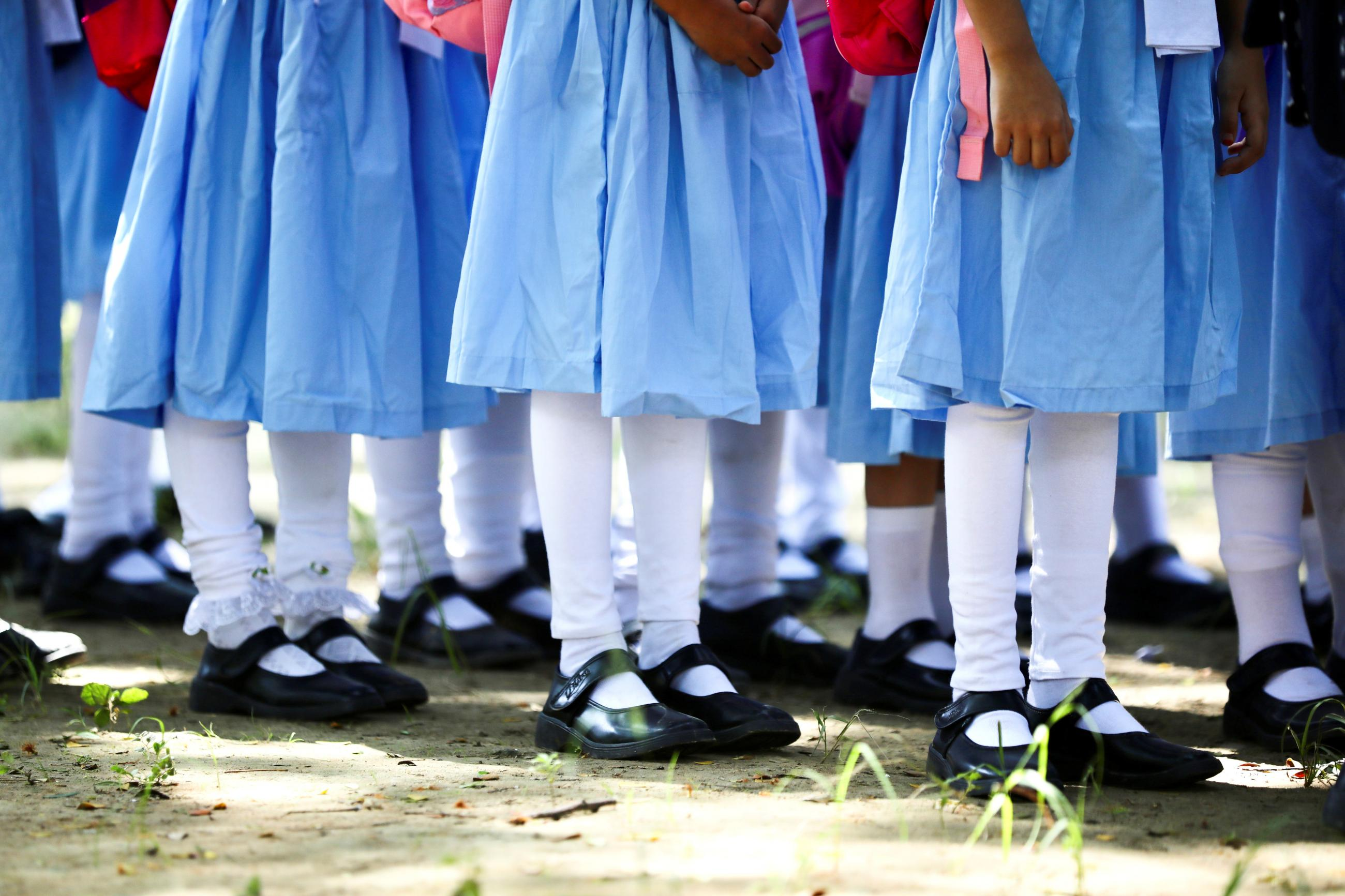 The legs and feet of students wearing blue dresses, white stockings, and black shoes can be seen standing in queues at the Viqarunnisa Noon School & College, in Dhaka, Bangladesh, September 12, 2021.