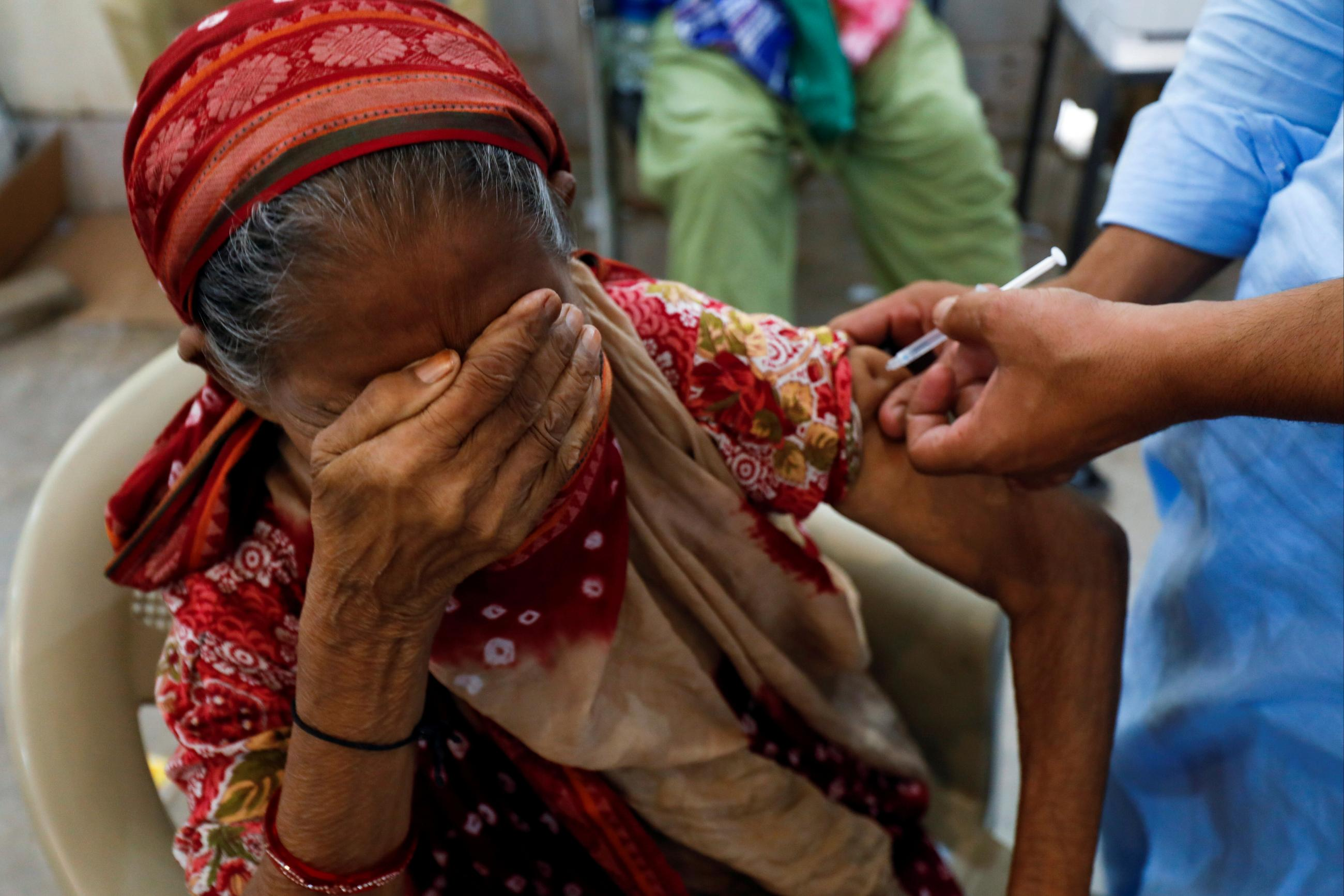 A woman, Basanti, 71, reacts as she receives a dose of the COVID-19 vaccine at a vaccination center in Karachi, Pakistan, on June 9, 2021.