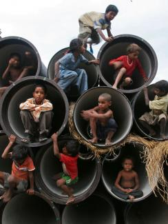 Picture shows several rows of large, concrete sewer pipes stacked on top of each other with their fat openings facing the camera. Each is large enough to fit one child huddled at the opening. About ten children can be seen climbing about on the feature.
