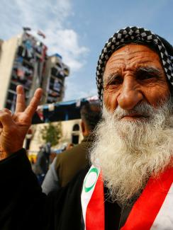 An elderly demonstrator poses for the camera as he makes a V-sign during ongoing anti-government protests, in Baghdad, Iraq, December 10, 2019. He has a black-and-white checkered scarf tied on his head and a red and white sash with green accents, around his neck. He has a very long white beard and friendly eyes.