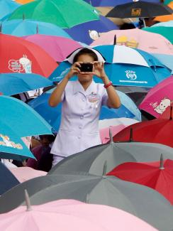 A nurse at a rally in Bangkok, Thailand. She stands among a sea of brightly colored umbrellas wearing a traditional nurse's uniform and facing the camera taking a picture in the direction of the viewer