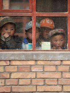 We see the adorable faces of several small children looking out weather-beaten window panes hung on a yellow brick wall. Faded chalk writing of chinese characters can be seen scribbled on the concrete sill.