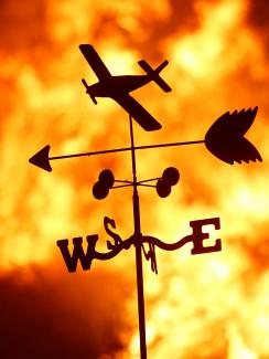 "Picture shows a thin metal toy-like vain with a plane, and arrow and a ""NESW"" directional indicator silhouetted against a burning fire."