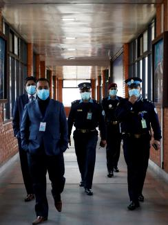 The picture shows three officers in full uniforms and two officials wearing suits walking toward the camera down a long air terminal corridor with windows on both sides.
