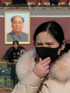 The photo shows a woman in a black mask in the foreground with a huge portrait of Chairman Mao visible in the background, along with a uniformed officer standing guard.