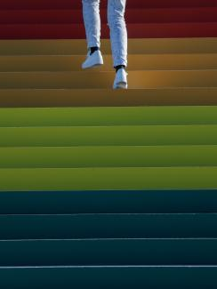Photo shows the legs and feet of someone wearing white pants and white sneakers walking up a wide staircase that fills the frame and is brightly adorned in rainbow hues. This is a striking photo.