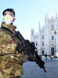 The photo shows a soldier in full combat gear wearing a mask and holding a military-style assault rifle. In the distance is the iconic architectural tourist destination.