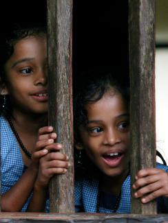 The picture shows twin girls smiling as they peek out the window.