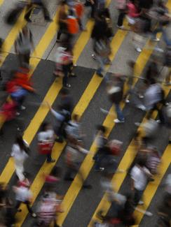 Picture shows the street from above, a wide pedestrian walkway with broad yellow lines painted at an angle. Dozens of people can be seen in the frame, all blurred due to fast movement and a slow shutter.