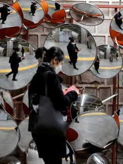 This is an amazing image of a woman walking by a display of spherical mirrors, the sort of which someone might place on a corner to see a wide angle. She is wearing a black face mask and is reflected in all the mirrors.