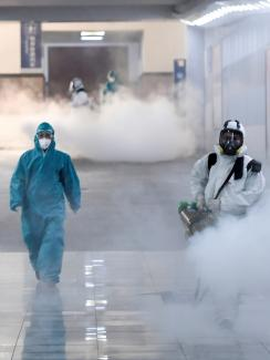The photo shows several people clad head-to-toe in protective suits fogging what is presumably a disinfectant in thick clouds.