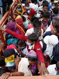 The photo shows the back of a flatbed truck from above. People are packed in the vehicle beyond capacity, sardined together for what looks like a bumpy ride.