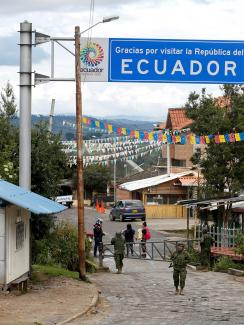 "The photo shows a simple border crossing through a small town with a big sign reading ""Ecuador"" above the street. The crossing is closed with metal barricades, and a soldier stands out front."