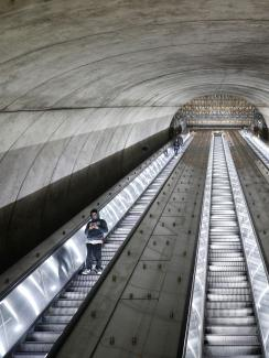 The picture shows a long escalator tube almost empty.