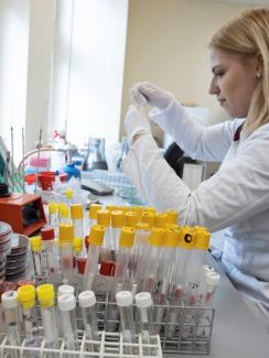 Picture shows a lab worker in a white lab coat sitting at a bench surrounded by test tubes preparing samples for analysis.