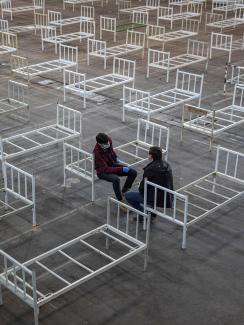 This is a striking image of two people resting on the edge of plain metal bed frames in a large space in which many, many more bed frames are placed.