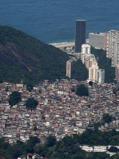 The photo is a gorgeous shot taken from the sky showing the slums cascading down the mountain to the coast, which is dotted with modern skyscrapers, and the ocean beyond.