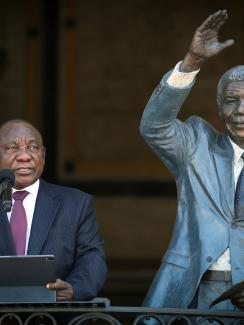 The images shows the president standing next to a life-sized statue of Nelson Mandela.